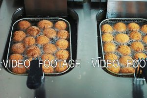 Donuts are fried in boiling oil in the deep fryer. Hot oil, high temperature roasting. Cooking