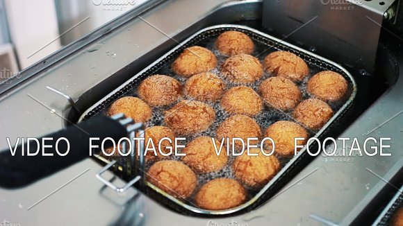 Donuts In Hot Oil In The Deep Fryer Cooking In The Restaurant Hot Boiling Oil In The Deep Fryer