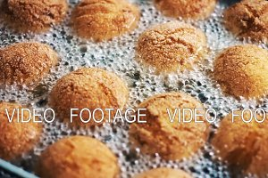 Donuts in boiling oil in a deep fryer close-up. Cooking, fast food.