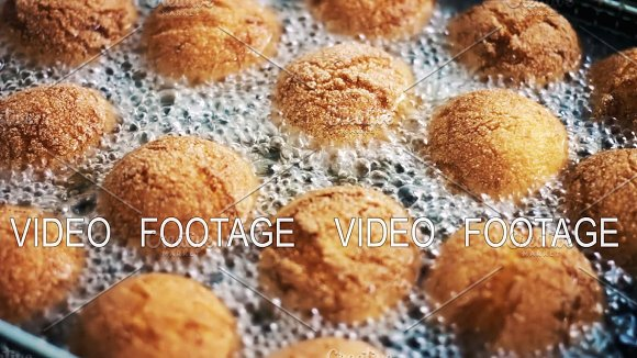 Donuts In Boiling Oil In A Deep Fryer Close-up Cooking Fast Food