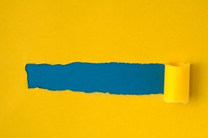 Yellow torn paper with blue space fo