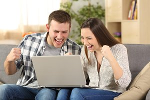 Excited couple reading news on line