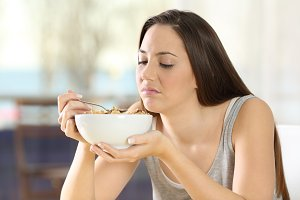 Disgusted woman eating cereals