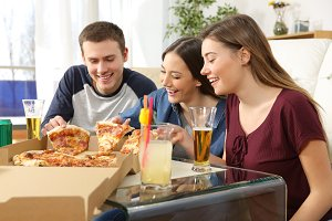 Friends talking and eating pizza