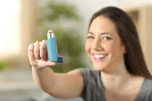 Girl showing an asthma inhaler