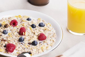 Cereal bowl breakfast with milk, raspberries and blueberries next to orange juice and decoration plant. Vertical studio shot.