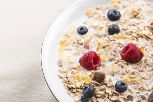 Plate of cereals with milk, raspberries and blueberries.