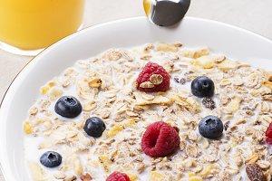 Cereal bowl breakfast with milk, raspberries and blueberries next to orange juice. Vertical studio shot.