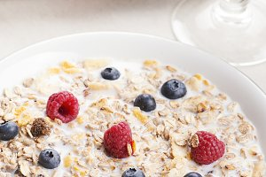 Cereal bowl breakfast with milk, raspberries and blueberries next to a glass with blackberries. Vertical studio shot.