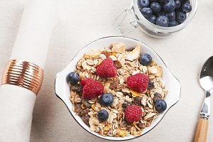 Top view of breakfast cereal with raspberries and blueberries alongside napkin and spoon.