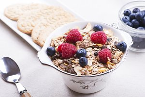 Breakfast cereal with raspberries and blueberries next to plate with cookies.