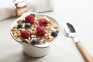 Breakfast cereals with raspberries and blueberries next to spoon.