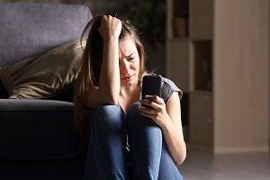 Sad teen checking phone