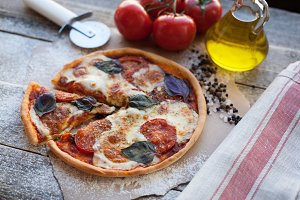 Appetizing pizza margarita on a wooden table in daylight. Vegetarian dish. Top view
