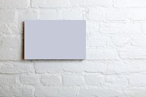 lilac blank poster in a white brick wall. Template Mock up for your content