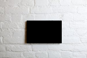 Black blank poster in a white brick wall. Template Mock up for your content