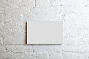 White blank poster in a white brick wall. Template Mock up for your content