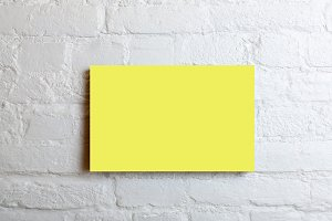 yellow blank poster in a white brick wall. Template Mock up for your content