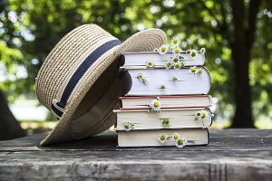 Books with wild flowers and hat