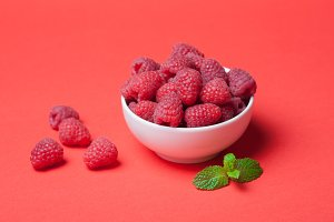 Bowl with fresh raspberries and mint leaves on a red background. Copy space. Minimal concept. hard light