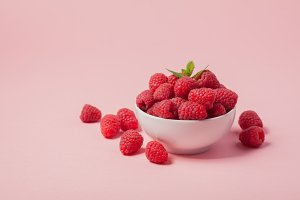 Bowl with fresh raspberries and mint leaves on a pink background. Copy space. Minimal concept