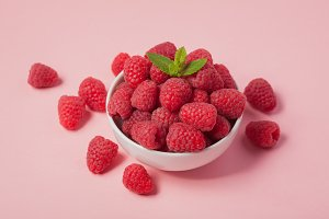 Bowl with fresh raspberries and mint leaves on a pink background. Minimal concept