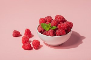 Bowl with fresh raspberries and mint leaves on a pink background. Copy space. Minimal concept. hard light