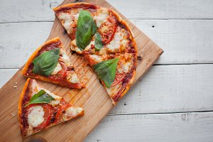 Delicious Italian pizza Margherita on a white wooden table. Top view