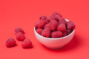 Bowl with fresh raspberries on a red background. Minimal concept. Copy space