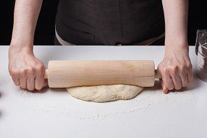 Female hand rolled pizza dough with a rolling pin on a white table, sprinkled with flour