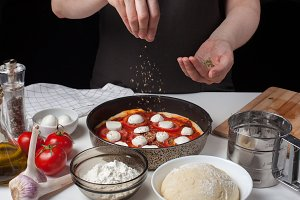Hands of the woman cook sprinkle Italian raw pizza margarita oreano on a dark background. On the white table lie the ingredients of mozzarella, garlic, yeast dough, flour and olive oil