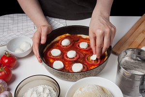 Female chef adds cheese to mozzarella to make homemade pizza. On the white table are mozzarella, pizza dough, and garlic.