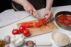 Female chef cuts the tomatoes for making homemade pizza. On the white table are mozzarella, pizza dough, and garlic