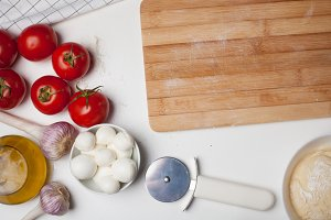 Wooden cutting Board with ingredients for homemade pizza on a white table