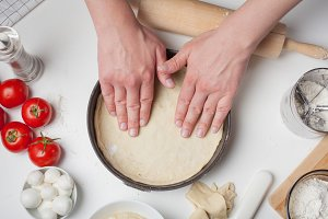 Male chef puts the rolled out dough in a pizza shape. On the white table are the tomatoes, mozzarella balls, olive oil and flour