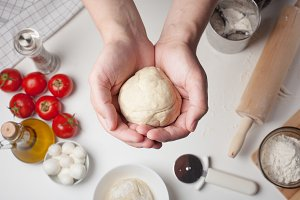Men's hands hold the ball of dough for pizza on a table and ingredients. On the white table are the tomatoes, mozzarella balls, olive oil and flour