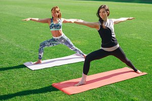 Two young women in sportswear doing yoga on the grass at the stadium