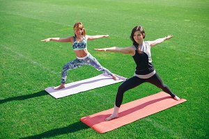 Beautiful sporty fit yogini women practices yoga asana - warrior pose.