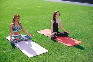 Two young women meditate sitting on a green lawn