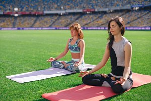 Group of people meditating in lotus pose on the stadium.