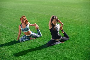 Two young yoga female doing yogatic exericise at the stadium.