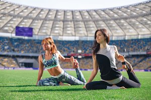 Young beautiful women doing yoga in morning at the stadium