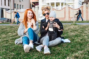 Mom and aunt play with a boy in the Park