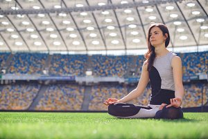 Young happy sporty girl sitting in yoga pose at the stadium