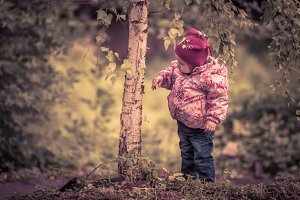 Little girl looks at the birch