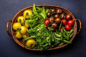 Red and yellow tomatoes, watercress salad and green pea on try. Harvest or clean healthy eating concept. Top view