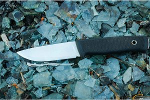 Sweden outdoor knife. Background colorful. Glass. Horizontal position