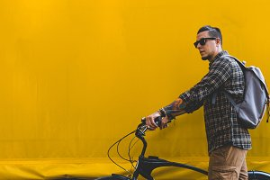 A young male traveler in sunglasses and with a backpack walks along a yellow wall with a bicycle