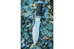 Military knife. Background colorful. Glass. Vertical position.
