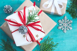 Several Christmas boxes of gifts festively decorated On a turquoise background, selective focus